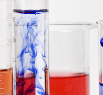 Several graduated cylinders of various thickness and heights with white side markings in front of a large beaker. They are all filled about halfway with red or blue chemical compounds. The blue ink is showing signs of Brownian motion when dissolving into water.